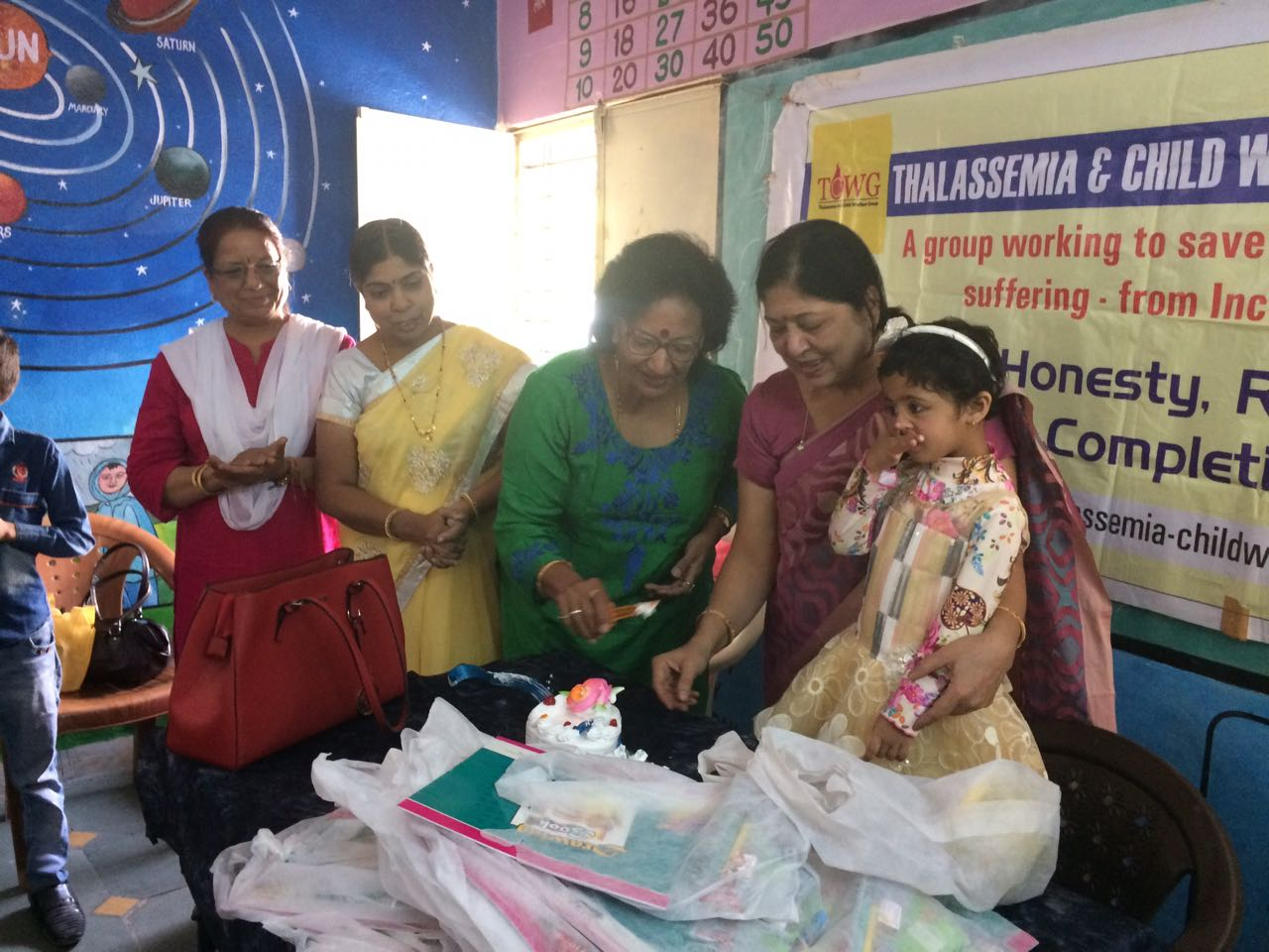 Distribution of cake drawing copy colours biscuits to students of nursary class in school no 124 on the occasion of birthday of vanya grand daughter of sandhya Panchayti its a event of TCWG